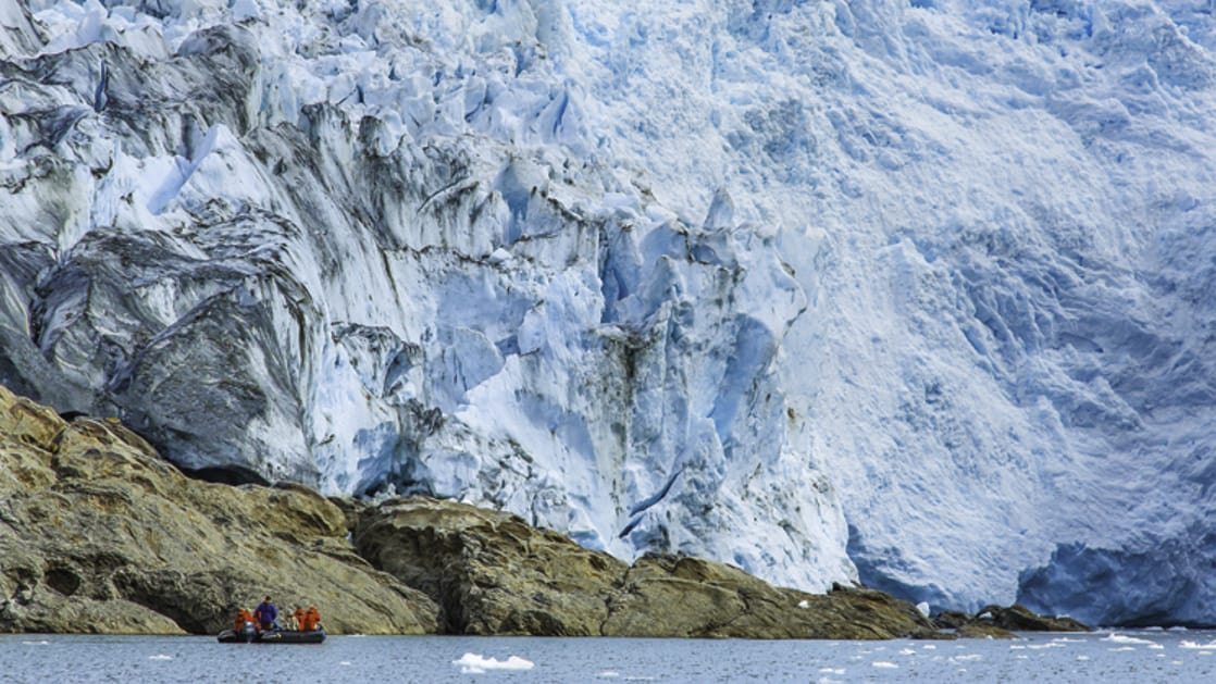 Zodiac with passengers from a small ship cruise up close to the face of a glacier in Patagonia