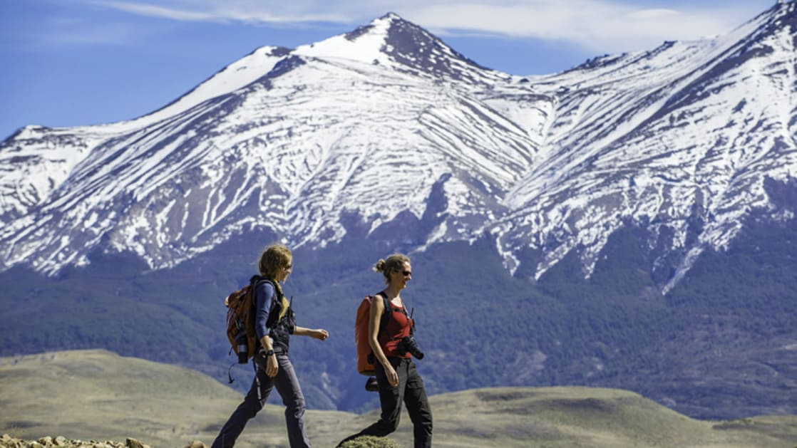 Two hikers at Torres del Paine National Park, Chile with jagged snowy mountains behind them