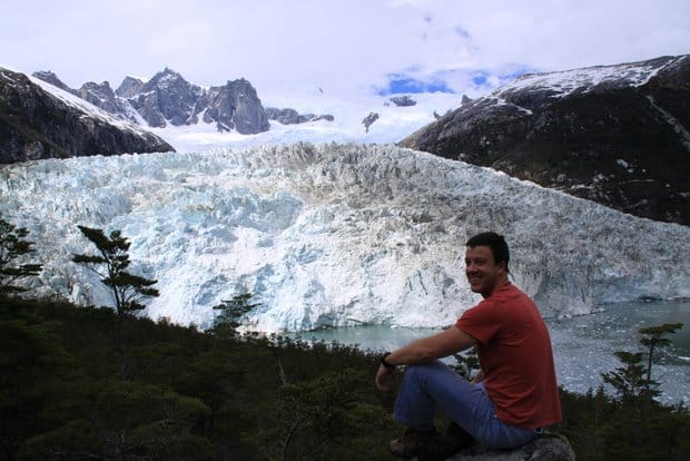 A traveler smiling while sitting and looking at a tidewater glacier in Patagonia.