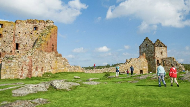 2 travelers walk toward old brick castles atop bright green grass under a blue sky on the Circumnavigating the Baltic Sea Cruise.