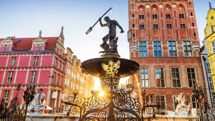 Sunrise over a Greek-god-stylized fountain with pink & orange buildings behind, seen on the Circumnavigating the Baltic Sea Cruise.