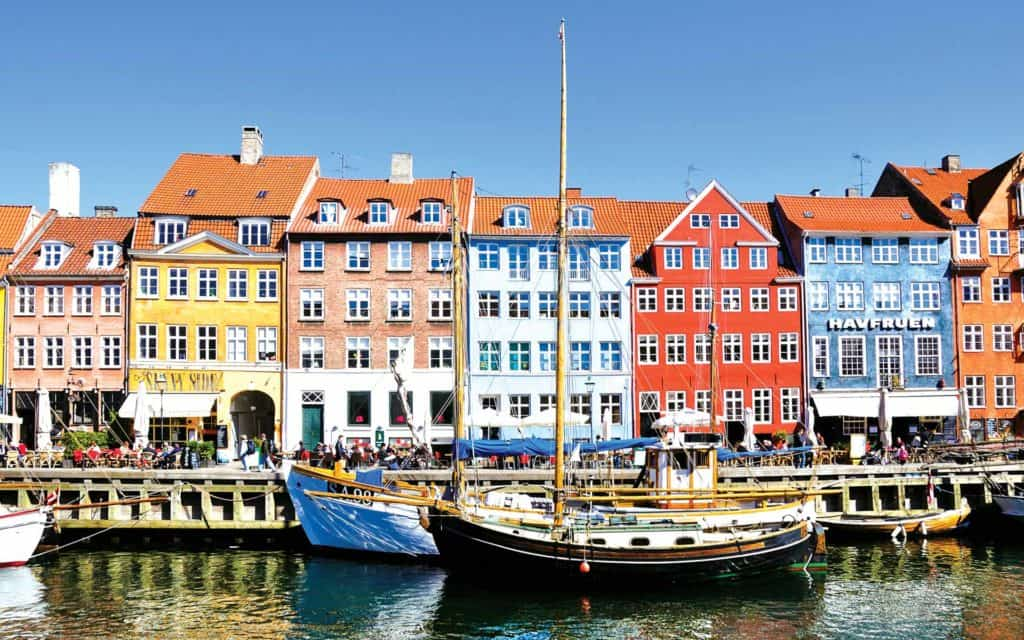Colorful buildings in Nyhavn along the Waterfront in Copenhagen with several small ships in front