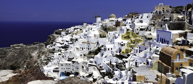 The Greek island of Santorini with white buildings and structures blanketing a hillside.