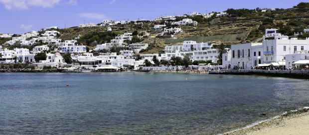 The Greek town of Mykonos from the shoreline with white structures scattered through out a hillside.