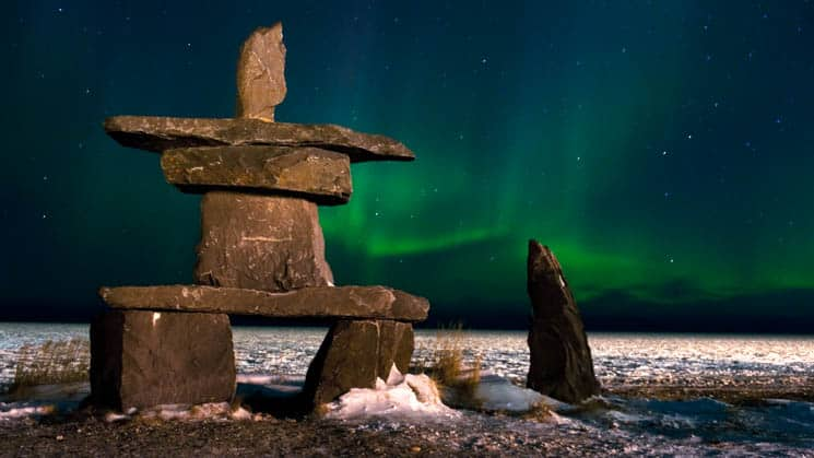 A rock statue in Churchill, Canada with green northern lights shining.