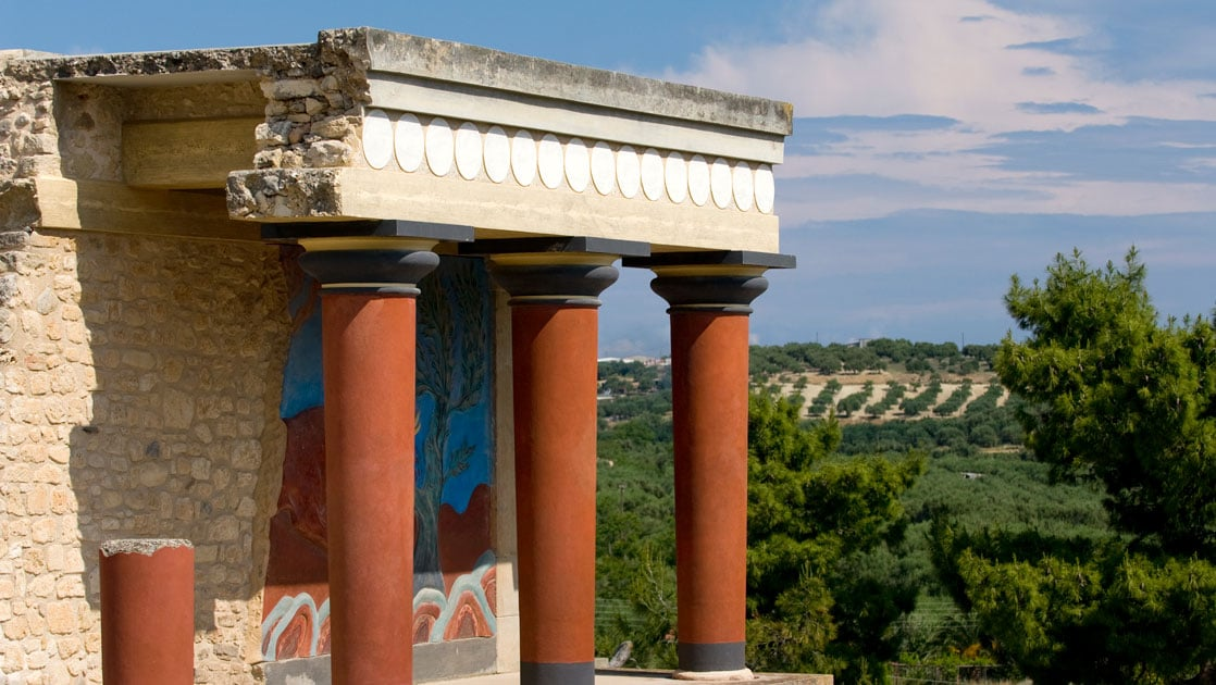 Red Greek pillars support an ancient stone building shown on a sunny day during a Greece cruise.