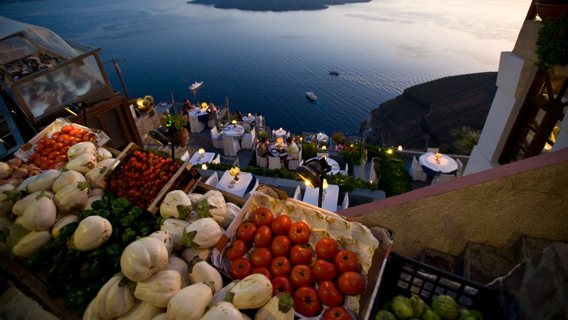Vegetables laid out in boxes look down on travelers dining on a terrace overlooking calm seas at sunset in Greece.