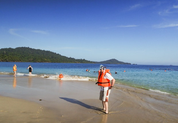 Traveler in a orange life vest on the beach after a snorkel with other travelers frolicking on the beach and water.