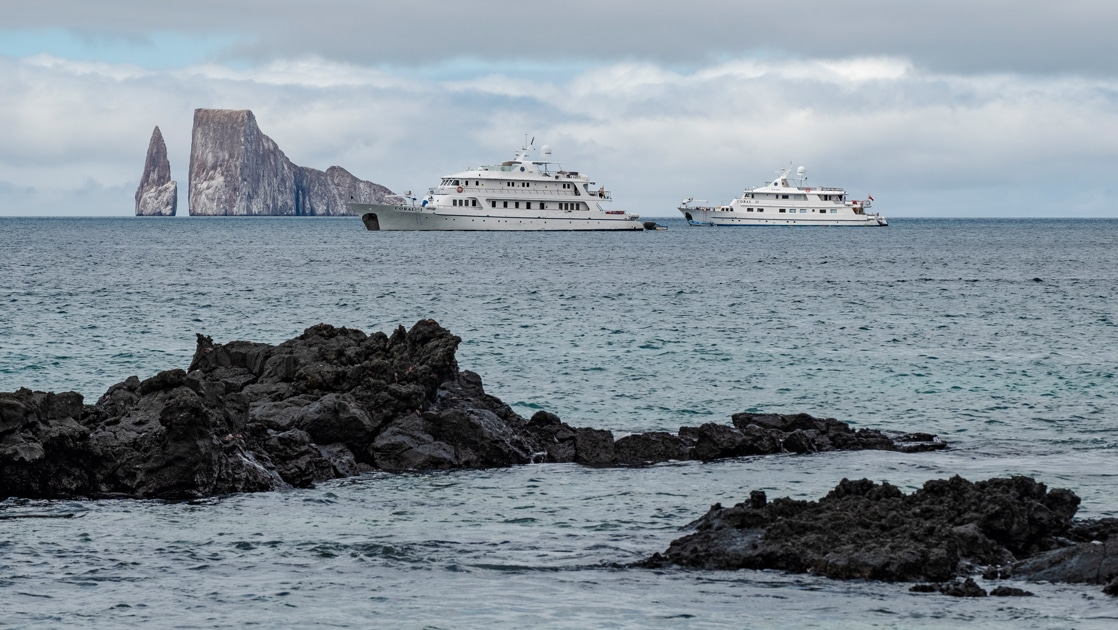 The all white Coral I and Coral II Galapagos cruise ships float on the horizon in front of Kicker Rock in the Galapagos Islands.