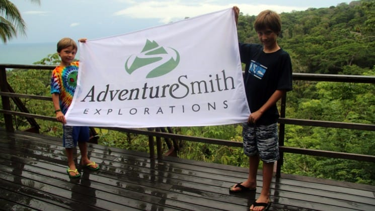 two boys holding adventuresmith explorations sign on costa rica family adventure
