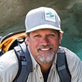 adventuresmith explorations founder and president todd smith wearing a hat and backpack smiling in front of an alaskan glacier