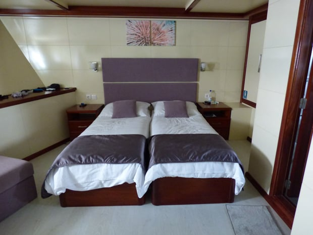 Stateroom on the small motor yacht Futura with 2 twin beds put together and nightstands.