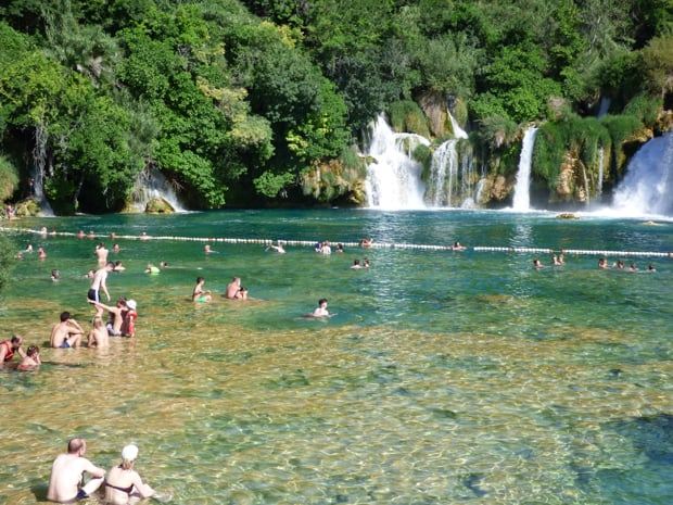 Krka National Park in Croatia with several waterfalls dropping into a big swimming hole with several tourists swimming or sitting about.