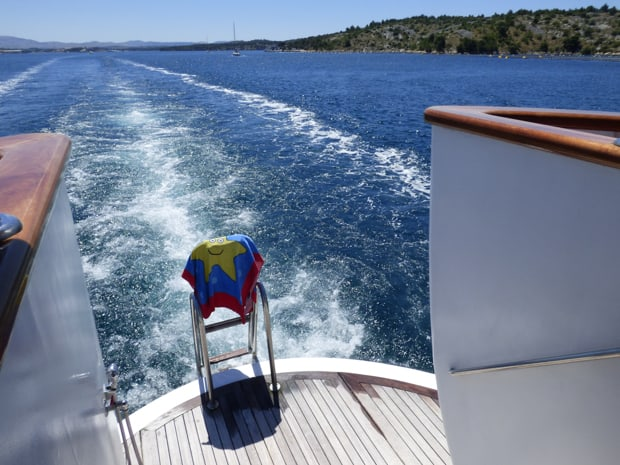 Swim step on the stern of the Futura as its cruising with a happy blue starfish towel placed on top of the ladder.