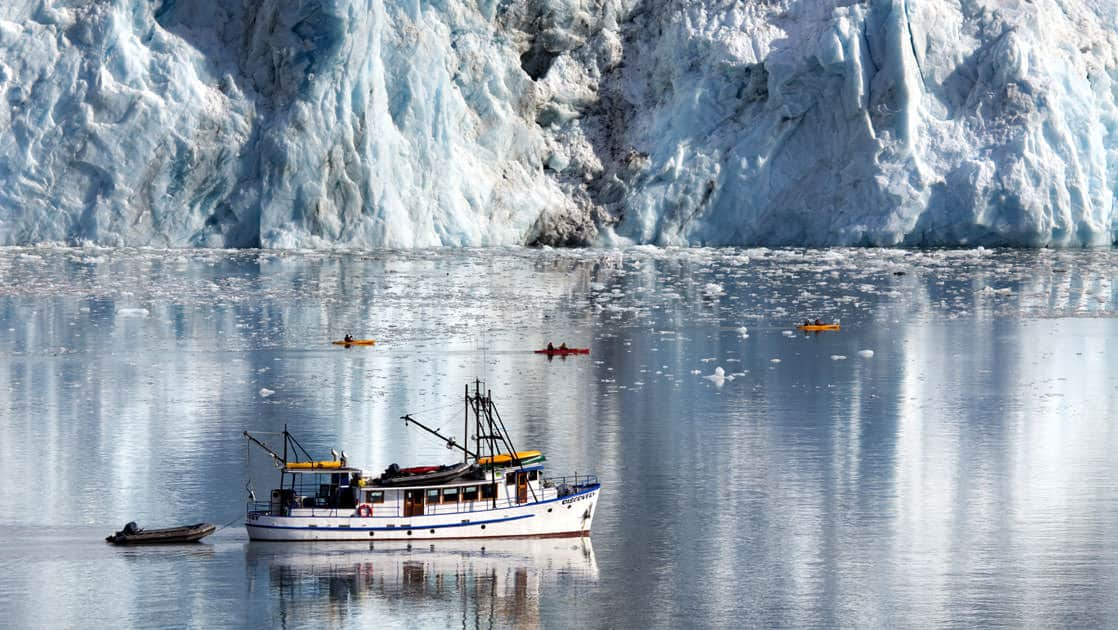 M/V Discovery with several kayaks and a skiff in front of the Cascade glacier with icebergs floating in Barry Arm, Chugach National Forest of Prince William Sound in Alaska