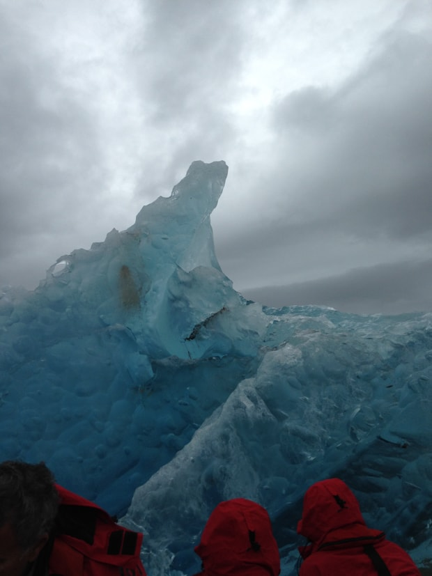 Small ship cruise guests up close to blue iceberg in the Arctic.