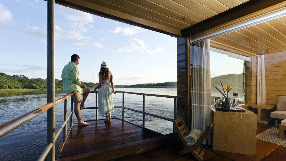 two small ship cruise passengers stand on the balcony overlooking the river on a sunny day with the jungle in the distance on the delfin amazon river cruise