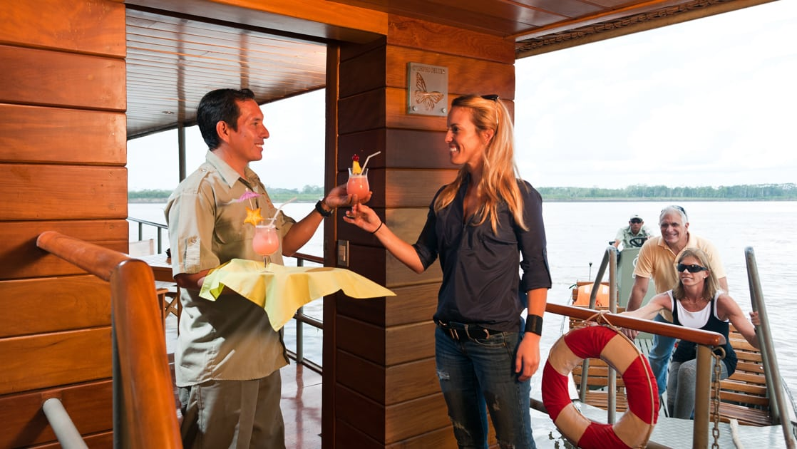staff member gives a small ship passenger a colorful cocktail as more travelers board the small ship on the delfin amazon river cruise