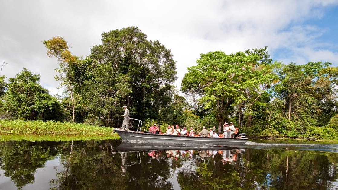 group of small ship passengers cruises down the amazon in skiff on a sunny day with trees behind them with a guide standing at the front