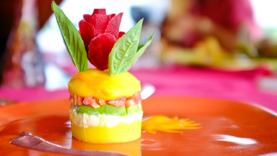 colorful cylinder of layered fruit with mint leaves coming out of the top on a colorful plate on the delfin amazon river cruise