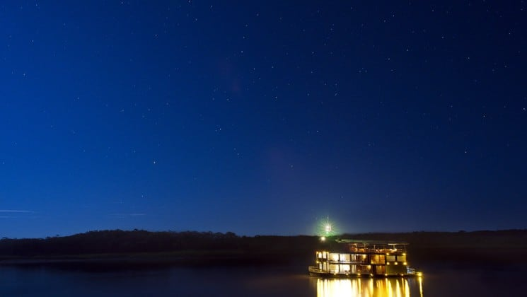 delfin i small ship illuminated at night cruising in the amazon with jungle behind it