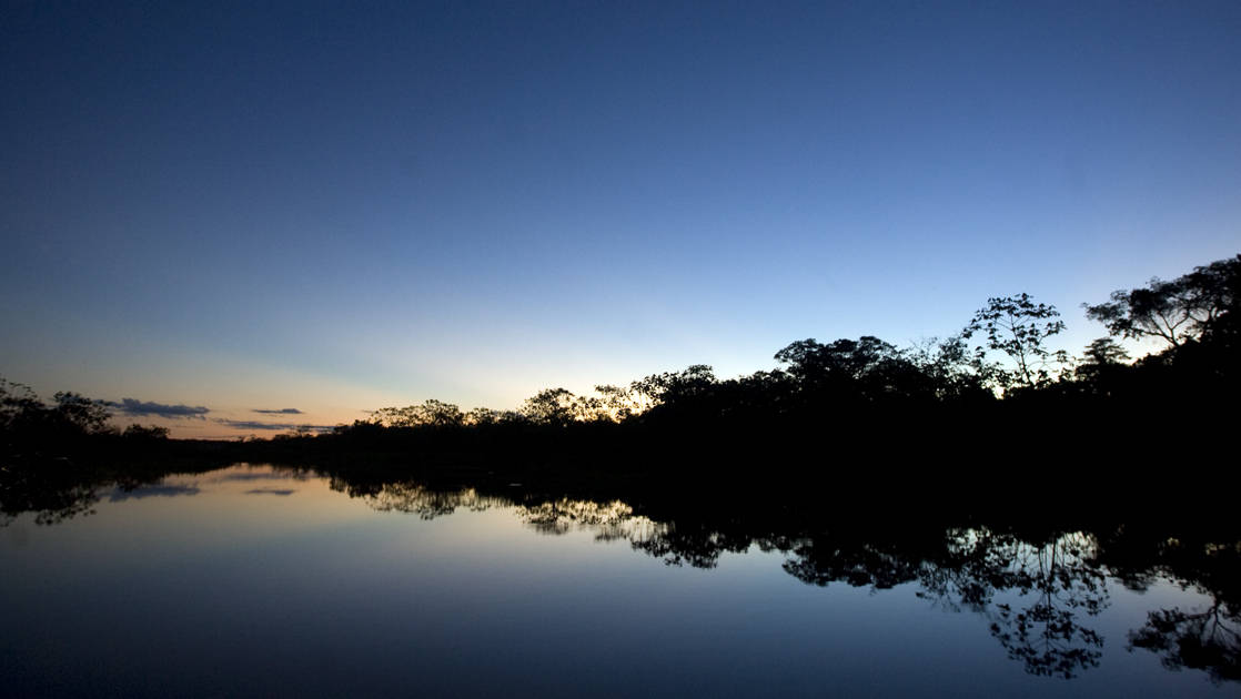 looking down the river at night on the delfin amazon river cruise with silhouettes of trees on either side and clouds in the distance