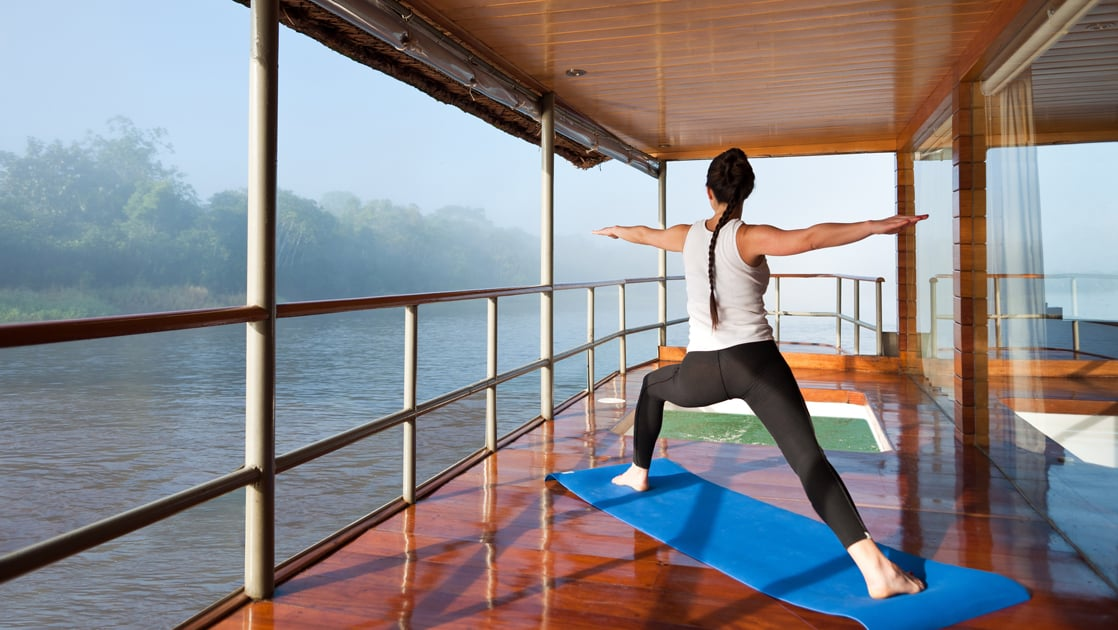 woman traveler doing yoga on the deck of the delfin i amazon small ship with the river in front of her and misty jungle in the distance