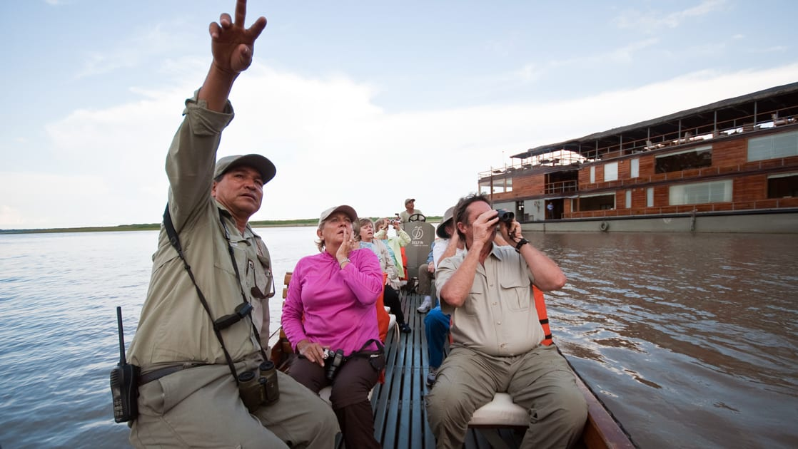 a guide points up to the sky in a small boat as travelers look up and take pictures on the delfin amazon river cruise, with the small ship anchored behind them