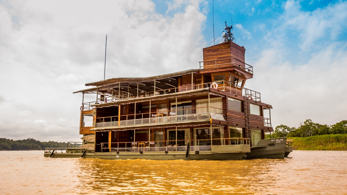 Delfin I Amazon river boat cruises through muddy water on a sunny day, with 3 wooden decks & 2 sage green metal hulls.