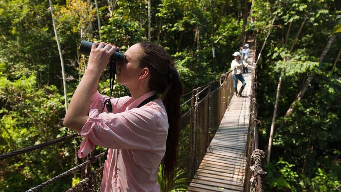 female traveler looks through binoculars while standing on a canopy bridge on the delfin ii amazon river cruise