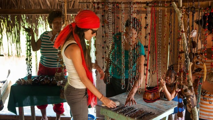 female traveler looking through items in a hut in a community market with other travelers and villagers around her on the delfin ii amazon river cruise