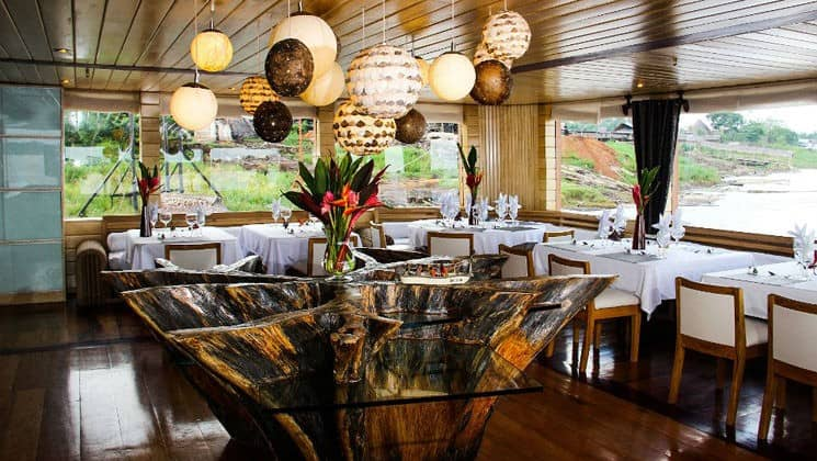dining room of the delfin ii amazon small ship, outfitted with luxurious chairs and tables sourced from the region