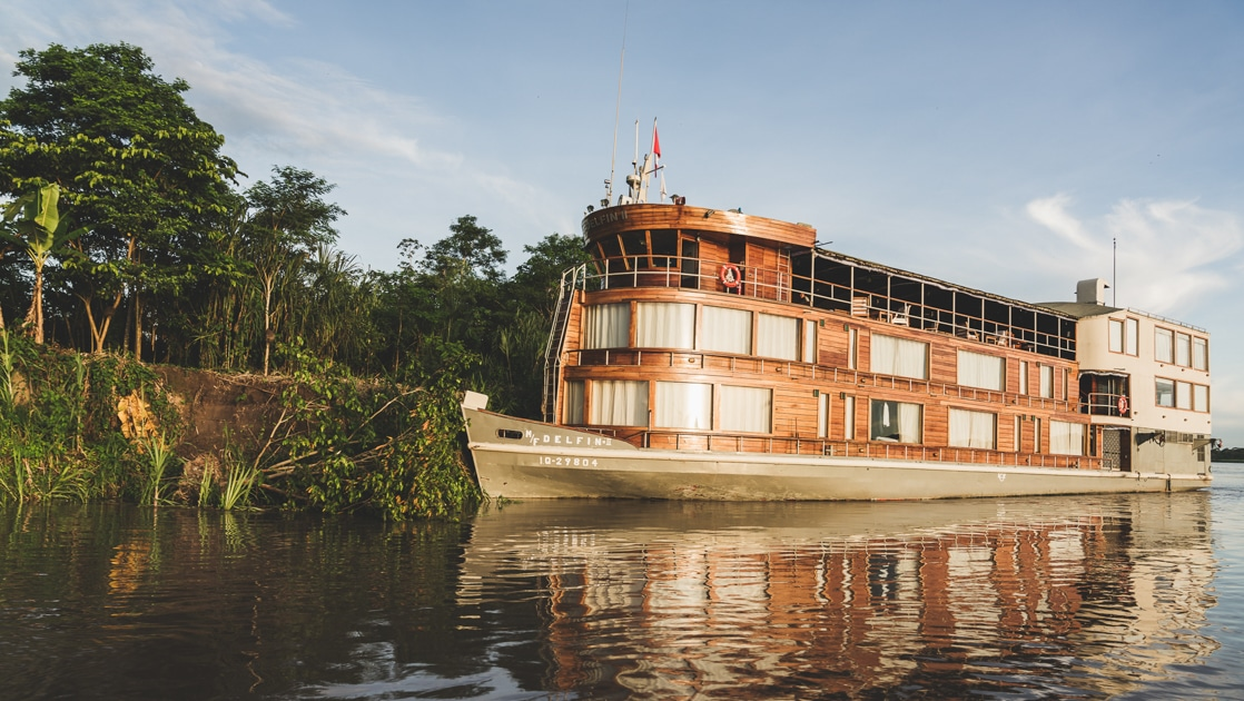 Delfin II Amazon river boat sits in glassy water beside the riverbank, with 3 wood-wrapped decks & a single sage green hull.