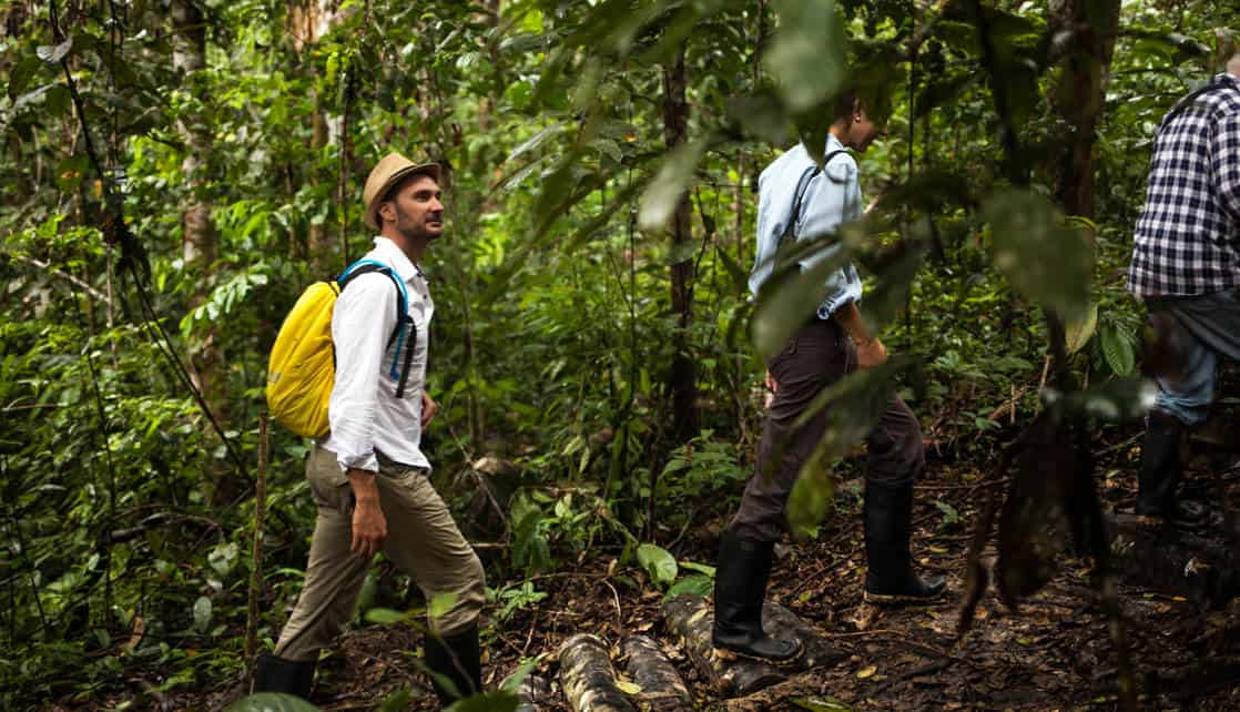 male traveler with a hat and yellow backpack walks behind other travelers through the jungle on the delfin ii amazon river cruise