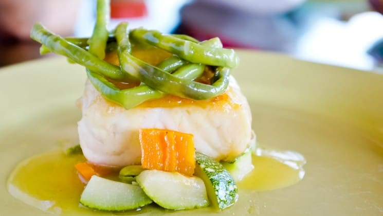 delectable fish entree with vegetables on top of and around it on the delfin ii amazon river cruise