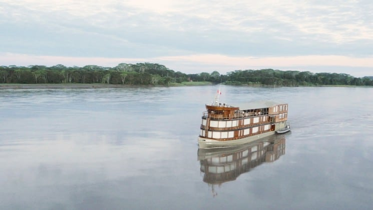 looking down at the delfin ii amazon small ship cruising on calm water on a partly cloudy day in the amazon