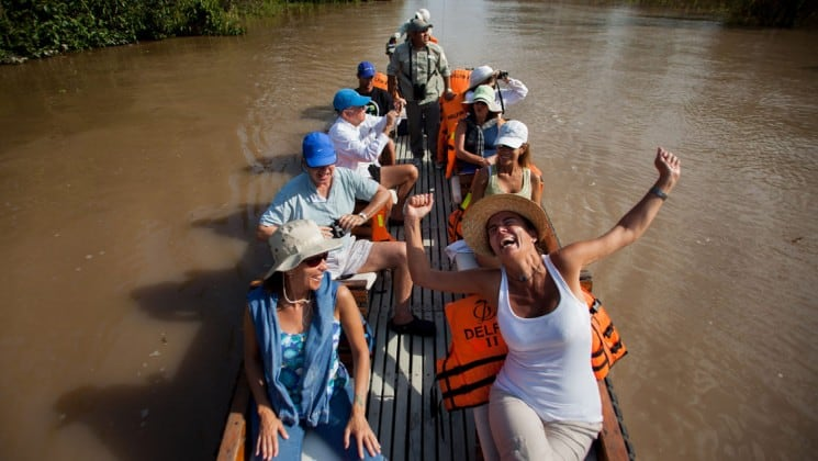 looking down at a group of delfin ii amazon river cruise small ship passengers in a skiff, with the woman in front smiling and throwing up her arms