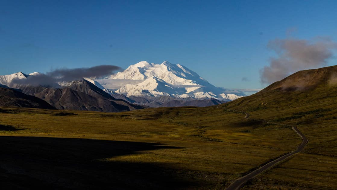 A lone road going through open field in denali national park with snow covered mountains behind