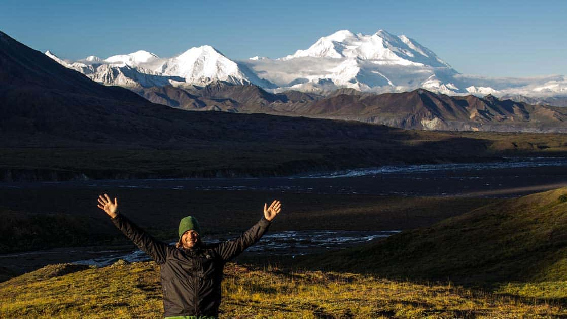Man smiling with his arms up in the air with a river and mountain range behind him in alaska's denali national park