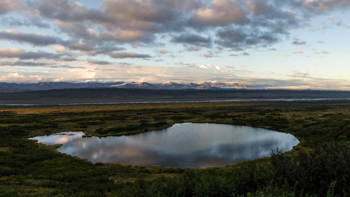 Small lake in the vast openness of denali national park in alaska with the reflection of clouds in the water and a mountain range in the distance