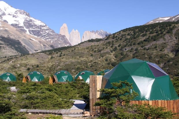 Eco tents lined across a valley floor with mountains and rock spires.