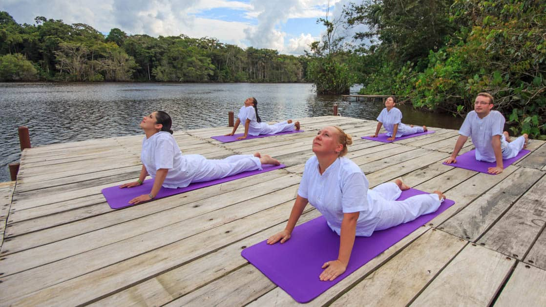amazon travelers doing yoga on purple mats on a dock at la selva ecolodge on a partly sunny day