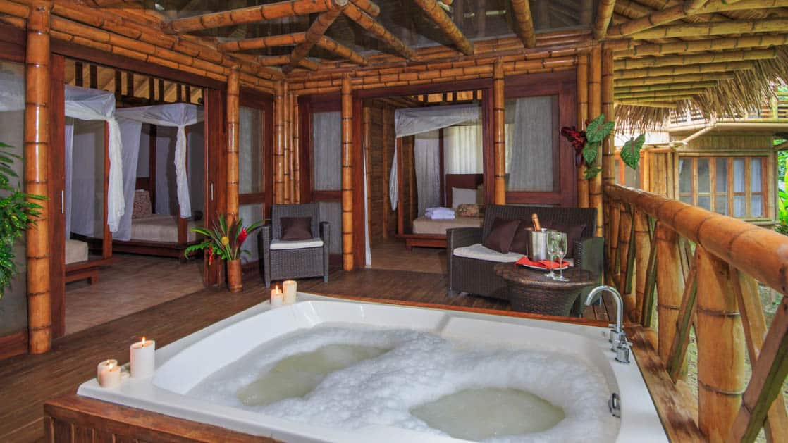 luxury amazon eco lodge room with high celings and a hot tub in the floor