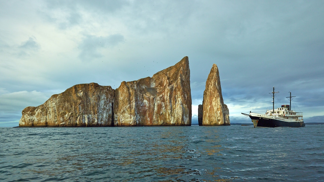 White and blue painted Galapagos small ship Evolution floats next to popular site Kicker Rock a tan volcanic cone that reaches up from the ocean.