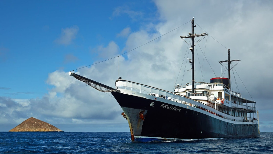 Motor yacht Evolution Galapagos ship painted dark blue and white with two large wooden masts for sails floats in front of a small island.