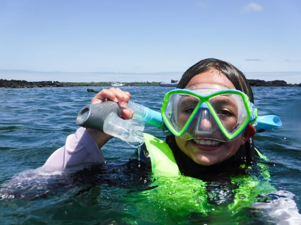 During a Galapagos cruise activity, A young girl snorkeling in the Galapagos on a blue sky day wearing lime green life jacket and mask.