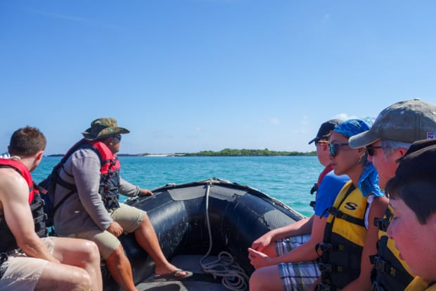 As part of a Galapagos cruise activity, A group of Galapagos travelers ride on an inflatable skiff with a guide, infront of them the blue cloudless sky drop to the teal water horizon.
