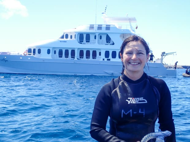A woman in a wetsuit in front of a Galapagos small ship smiling after snorkeling on a Galapagos small ship cruise