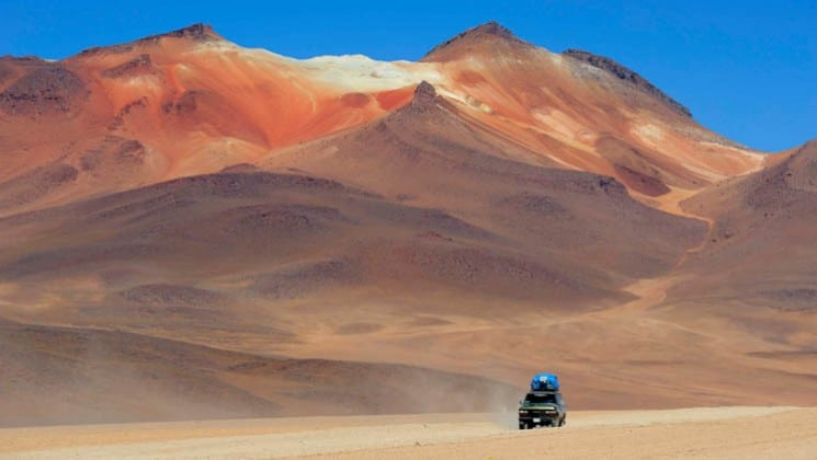 van on otherwise-deserted desert road in chile on explora atacama trip