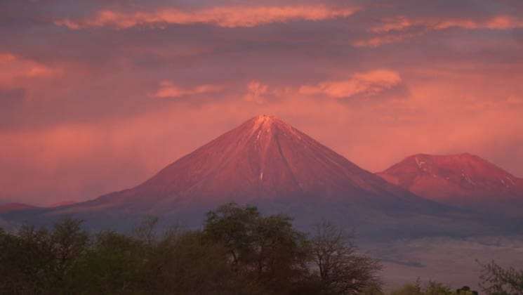 red and purple hues as sun sets over mountains on explora atacama land tour in chile
